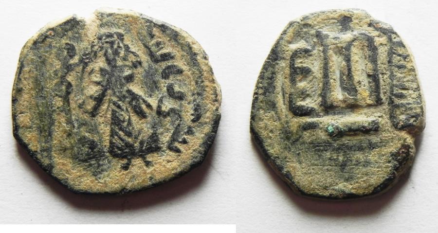 World Coins - ISLAMIC, Umayyad Caliphate. temp. 'Abd al-Malik ibn Marwan. AH 65-86 / AD 685-705. Æ Fals. Standing Caliph type. Aelia/Palestine mint. Struck circa AH 73-78 (AD 693-697)